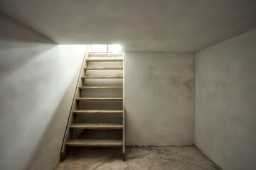 Fototapeta empty basement in abandoned old industrial building with little light and a wooden stairs