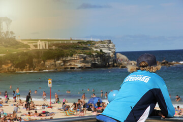 A lifeguard watching over the world famous Bondi Beach, which is very crowded.The sunny coast side in Sydney, Australia is a very big touristical attraction. A green cliff is visible in the background