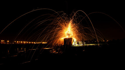 A man is standing on a sea container and is swinging sparks everywhere. The long exposure shows an explosion of fire. Concept of the dangers of fireworks and the life threatning infernos it can cause.