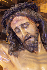 BARCELONA, SPAIN - MARCH 3, 2020: The detail of carved statue of Jesus on the cross in the chruch Santuari de la Mare de Deu del Carme (carmelites).