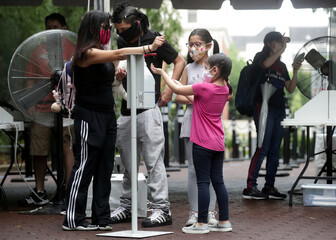 A family use a hand sanitizer station as the National Zoo reopens for socially-distanced patrons for the first time since the start of the coronavirus disease (COVID-19) outbreak in Washington
