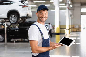 cheerful mechanic in overalls and cap holding digital tablet with blank screen in car service