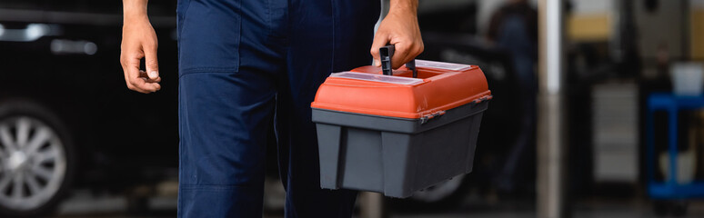 horizontal image of mechanic in uniform holding toolbox in service station