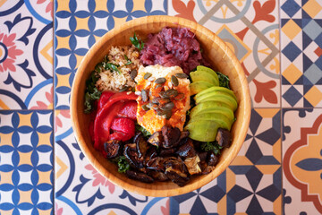 Buddha bowl, delicious vegan dish with fresh kale and avocado, roasted aubergines, red sauerkraut, couscous and humus with nuts and seeds positioned in a bamboo dish on a colorful ceramic tiles table