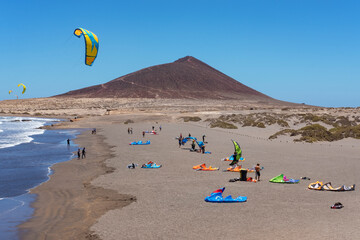 Montana Roja beach side with surfers enjoying a windy day practicing water sports such as kite surfing or kite boarding at El Medano, Tenerife, Canary Islands, Spain