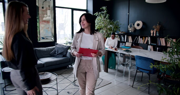 Camera follows successful happy middle aged Caucasian business woman walking around busy modern loft office slow motion.