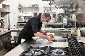 Chef in uniform cooking in a commercial kitchen. Male cook wearing apron standing by kitchen counter preparing food. High quality photo