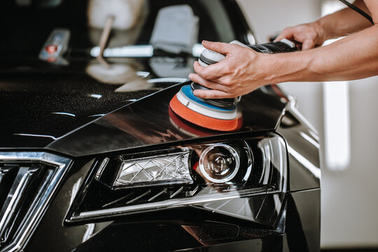 Professional detailing a car in car studio, hands with orbital polisher, scratching remover, vehicle care concept