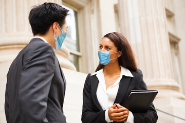 Two well dressed professionals wear face masks during the COVID-19 pandemic while in discussion...