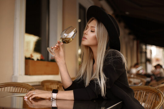 Model girl in with gentle makeup and blond hair enjoying wine at the cafe table in the summer evening