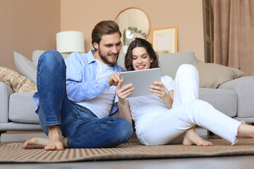 Happy couple sitting and planning new home decoration at home with a tablet, renovation and...
