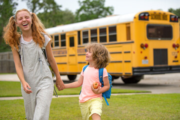 Happy Photo of two happy children looking out the windows of a yellow school bus. Plenty of space for text. Brother and sister standing together in front of school bus.