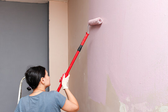woman painting wall with a roller in pink color