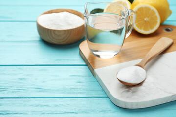Baking soda, vinegar and cut lemons on light blue wooden table