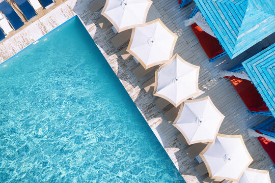 Lounge chairs with umbrellas near swimming pool on sunny day, top view