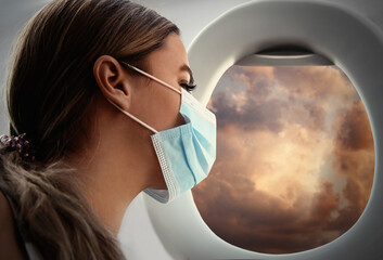 Traveling by airplane during coronavirus pandemic. Woman with face mask near porthole