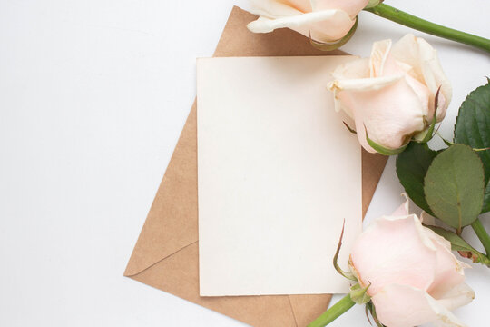 Minimalistic card mockup with roses. craft envelope, white flowers, branches, flat lay, top view. wedding invitation