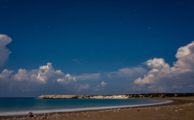 Sandy and pebble beach of the Mediterranean Sea, shot in calm weather at night with a long exposure.