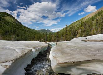 Mountain landscape. Spring melting snow on a mountain river.