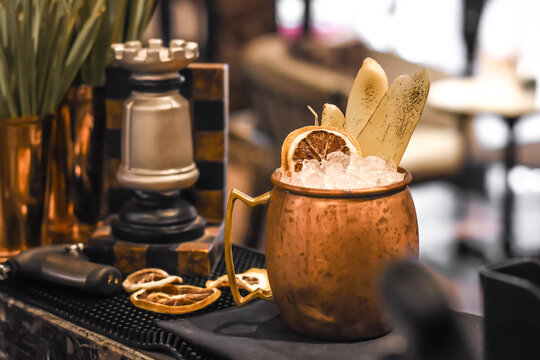 Signature cocktail decorated with burn ginger and Dehydrated lemon wheel in Mosco mule mug