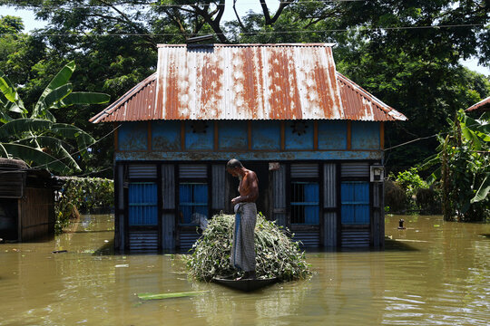 A man is seen on a boat after his house was flooded, after the flood situation worsened in Munshiganj district, on the outskirts of Dhaka