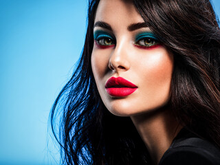 Portrait of beautiful young woman with bright blue makeup. Beautiful brunette with bright red lipstick on her lips. Pretty girl with long black hair. Closeup face of brunette woman. Sexy girl.