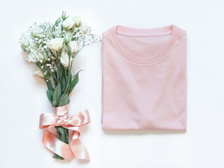 Mockup of a folded t-shirt placed near white flowers