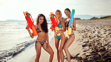 three women posing with water guns on a sandy beach