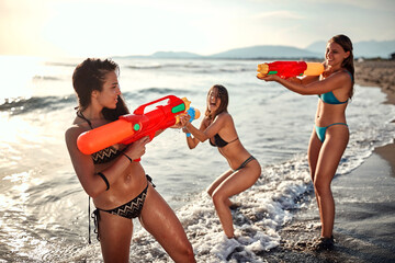 three young caucasian female friends playing with water guns on the  beach