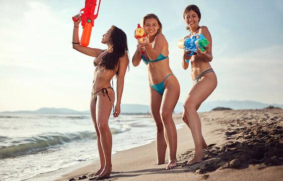 three beautiful women having fun on a sandy beach with water guns