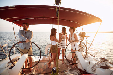 Friends drinking wine on the sunset on a yacht