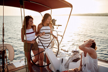 Young attractive girls enjoying the ride on a yacht
