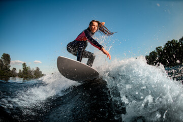 young female sportsman actively rides the splashed wave on surfboard