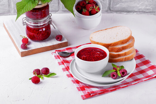Raspberry jam in white ceramic bowl and slices of white bread on the plate