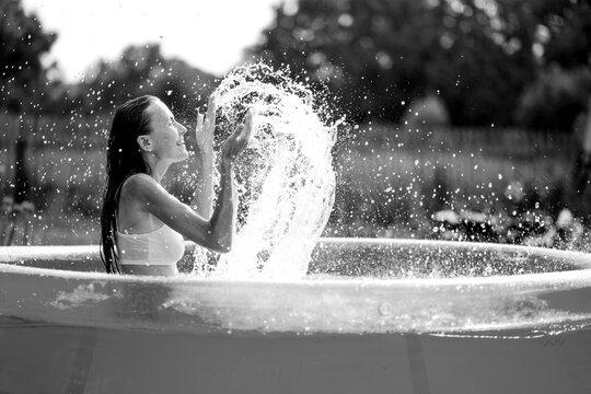 Beautiful woman splashing in inflatable swimming pool outdoor, having fun