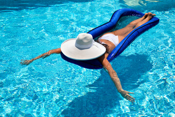Beautiful woman in a white hat lies on a mattress in the pool and relaxes