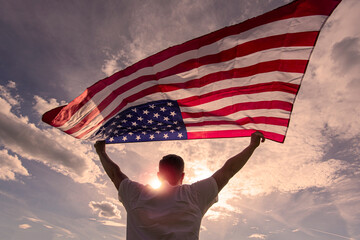 Man holding waving American USA flag in  hands during warm sunny evening in USA, concept picture