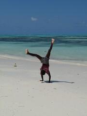 Young black boy doing handstand on white sand beach, Zanzibar,Tanzania