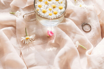 Wildflowers on background of soft beige fabric with daisy flowers in water in glass cup and...