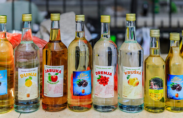Kotor, Montenegro - June 01, 2019: Selection of fruit flavored 100 proof homemade moonshine or rakija in reused bottles for sale at a market in the old town. Homemade printed labels