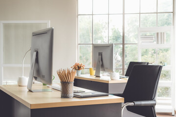 Desktop PC computers in small modern office or home office. Trendy workplace interior.