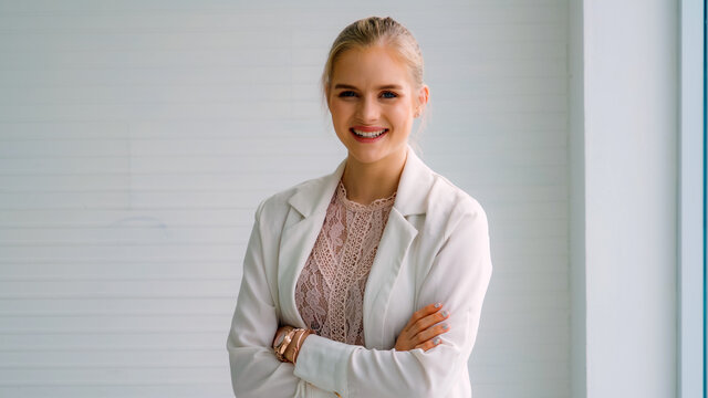 Attractive young woman profile portrait in office . Confident business person wearing formal suit working in corporate business.