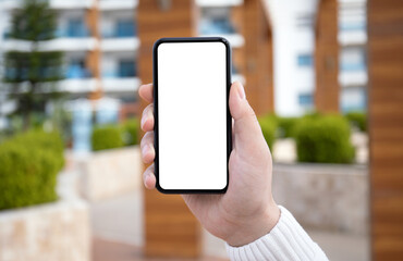 male hand hold phone with isolated screen in city background