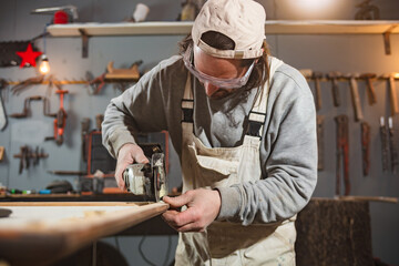 Male carpenter working on old wood in a retro vintage workshop. Wall mural