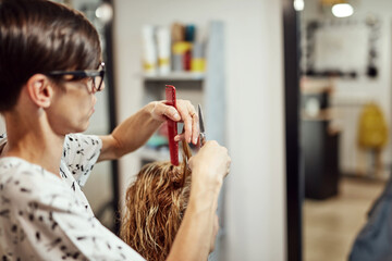 Hair dresser cutting hair in a saloon.