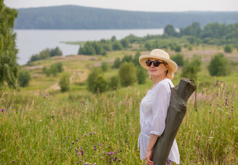 An elderly woman in an elegant straw hat is traveling in nature, enjoying the scenery. The concept of an active lifestyle for older people.