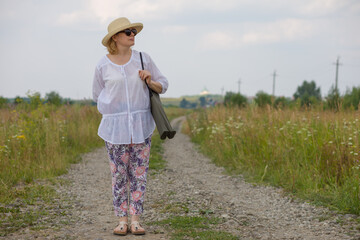 An elderly woman in an elegant straw hat stands on a rural road, enjoying the scenery. The concept of an active lifestyle for older people.