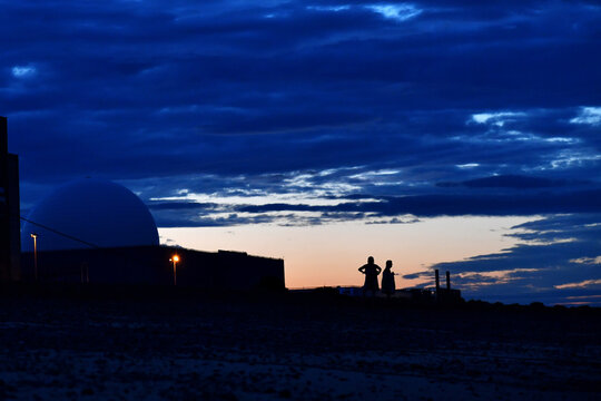 Beach walkers enjoy the sunset at Sizewell Nuclear Power Station in Sizewell