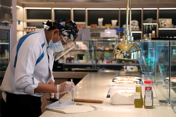 A member of the staff wears a mask and a face shield to prevent the spread of the coronavirus disease (COVID-19), at the canteen on the Explorer Dream cruise ship in Keelung