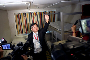 Chen Hsiu-Hsi, the associate Dean of the Department of Public Health from National Taiwan University explains the use of a negative pressure isolation room to the media on the Explorer Dream cruise ship in Keelung